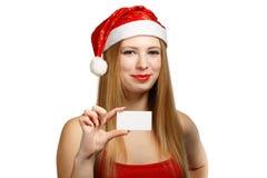 Junge Frau in Weihnachtsmann-Hut mit Weihnachtskarte Stockfoto