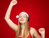 Junge Frau in Weihnachtsmann-Hut und Kopfhörer nehmen Vergnügen von stockbilder