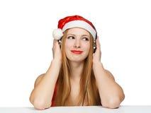 Junge Frau in Weihnachtsmann-Hut und -kopfhörern lokalisiert auf Weiß Stockbild