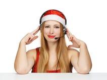 Junge Frau in Weihnachtsmann-Hut und -kopfhörern lokalisiert auf Weiß Lizenzfreies Stockbild