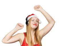 Junge Frau in Weihnachtsmann-Hut und Kopfhörer nehmen Vergnügen von Stockbild