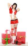 Junge Frau in Weihnachtsmann-Kostüm mit Geschenk stockbild