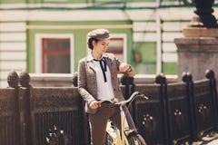 Junge Frau an Weinlesefahrrad-Briten-Art Stockfoto