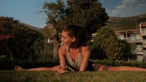 Junge Frau, welche die aufgeteilte Übung sitzt auf Gras am Sommermorgen tut stock video