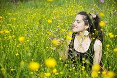 Junge Frau, welche die Blumen riecht Stockfotos