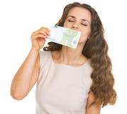 Junge Frau, welche die 100-Euro-Banknote schnüffelt Lizenzfreies Stockfoto