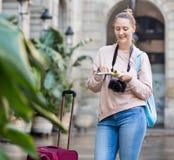 Junge Frau, welche die Flugschrift sucht nach Weg hat stockfotografie