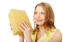 Junge Frau, welche die Geschenkbox rüttelt Lizenzfreies Stockfoto