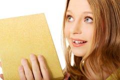 Junge Frau, welche die Geschenkbox rüttelt Stockbilder