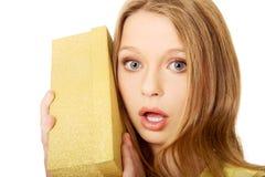 Junge Frau, welche die Geschenkbox rüttelt Stockfoto