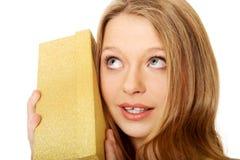 Junge Frau, welche die Geschenkbox rüttelt Stockfotos