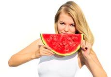 Junge Frau, welche die große Scheibe Wassermelonen-Beere frisch isst Stockbild