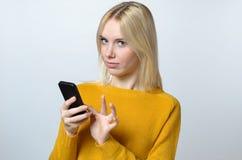 Junge Frau, welche die Kamera mit ihrem Handy betrachtet Stockfotos