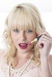 Junge Frau, welche die Lippenzähne halten roten Lippenstift leckt Stockfoto
