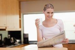 Junge Frau, welche die Nachrichten beim Trinken des Kaffees liest Stockbild
