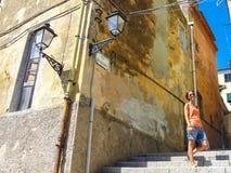 Junge Frau, welche die Sonne in einer Gasse eines kleinen ländlichen mittelalterlichen Dorfs genießt Stockfoto