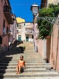 Junge Frau, welche die Sonne in einer Gasse eines kleinen ländlichen mittelalterlichen Dorfs genießt Lizenzfreie Stockbilder