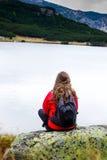 Junge Frau, welche die Stille von Gebirgssee bewundert Lizenzfreie Stockbilder