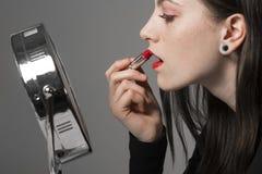Junge Frau wendet roten Lippenstift im Schminkspiegel an Lizenzfreie Stockfotografie
