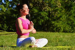 Junge Frau während der Yogameditation im Park Stockbilder