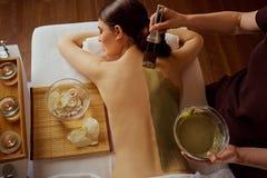 Junge Frau wird auf eine Maske auf ihr zurück in Badekurortsalon eingesetzt Lizenzfreie Stockfotografie