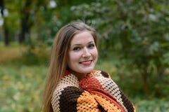 Junge Frau wird durch einen Schal gewärmt Stockbild