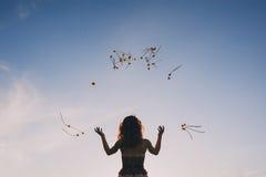 Junge Frau wirft gelbe Blumen in der Luft gegen einen Hintergrund des blauen Himmels stockfoto
