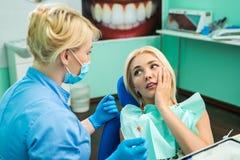 Junge Frau am Zahnarzt, der über eine Zahnschmerzen sich beschwert zahnheilkunde Doktor und der Patient lizenzfreie stockfotos