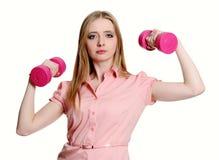 Junge Frau zeigt ihre Stärken, die Dumbbell anhalten Stockfotografie