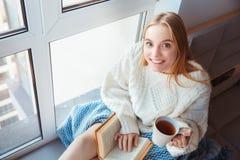 Junge Frau zu Hause, die auf Tee-Lesebuch des Fensterbrettwinterkonzeptes trinkendem sitzt stockfotos