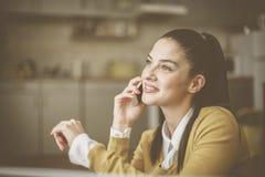 Junge Frau zu Hause, die am Handy spricht lizenzfreie stockbilder