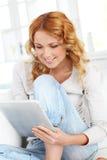 Junge Frau zu Hause mit Berührungsfläche Stockfotos