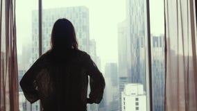 Junge Frau zum panoramischen Fenster, das heraus zu Hause Wohnung auf den Stadtgebäuden schaut 3840x2160 stock footage