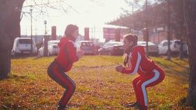 Junge Frau zwei in den Sportkostümen, die Hocken im Park tun stock video
