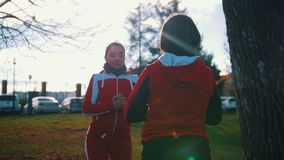 Junge Frau zwei in den Sportkostümen, die Hocken im Park vor einander tun stock video footage