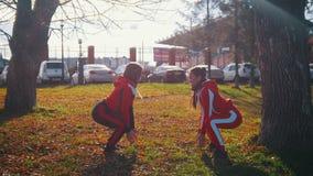 Junge Frau zwei in den Sportkostümen, die Hocken tun und in Park springen stock video footage