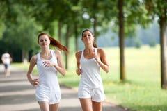 Junge Frau zwei, die in einen Park läuft Stockfotografie