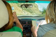 Junge Frau zwei, die mit dem Auto eine im Beifahrersitzblick reist lizenzfreie stockfotografie