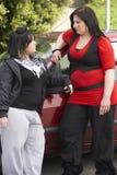 Junge Frau zwei, die nahe bei Auto steht Lizenzfreie Stockfotografie