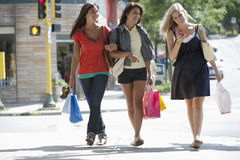Junge Frauen auf einer texting Einkaufenreise Stockfotos