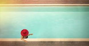 Junge Frauen in den Hüten im Pool Stockbilder