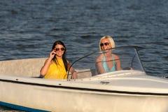 Junge Frauen in der Sonnenbrille, die im Motorboot sitzt stockfotografie