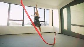 Junge Frauen des Brunette tanzen die rhythmische Gymnastik, die mit rotem Band im schwarzen sexy Kleid vor den Fenstern modern is stock video footage