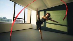 Junge Frauen des Brunette tanzen die rhythmische Gymnastik, die mit rotem Band im schwarzen sexy Kleid vor den Fenstern modern is stock footage