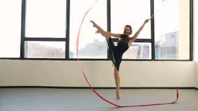 Junge Frauen des Brunette tanzen die rhythmische Gymnastik, die mit rotem Band im schwarzen sexy Kleid vor den Fenstern modern is stock video