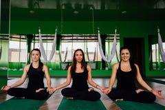 Junge Frauen des Porträts drei Freunde im Lotussitz auf der Matte nach Antigravitationsyoga trainiert Aero von der Luftfliege Stockbild