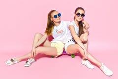 Junge Frauen, die auf Skateboard sitzen stockfotos