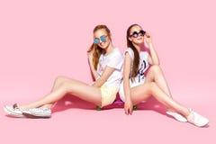 Junge Frauen, die auf Skateboard sitzen stockfoto