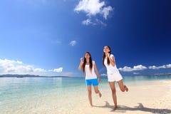 Junge Frauen, die auf Strand laufen Lizenzfreie Stockbilder