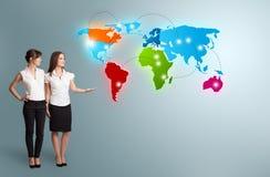 Junge Frauen, die bunte Weltkarte darstellen Lizenzfreies Stockfoto